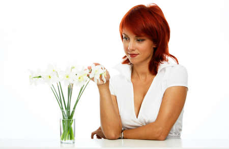 young smiling woman is looking at the flower photo
