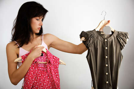 woman is deciding which dress to buy photo