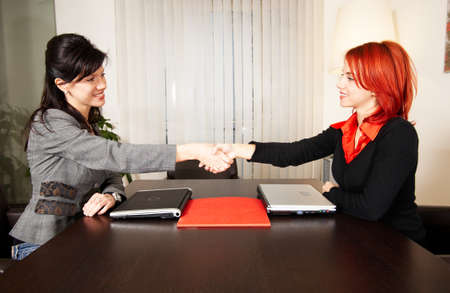 posing  agree: two young confident caucasian businesswomen after meeting