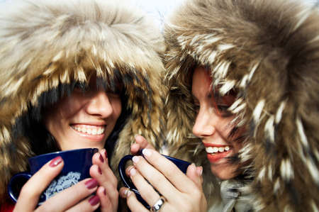 winters: two cute caucasian women are drinking mulled wine