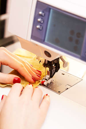 stitching machine: A hand of a dressmaker supporting a cloth while sewing on a sewing machine