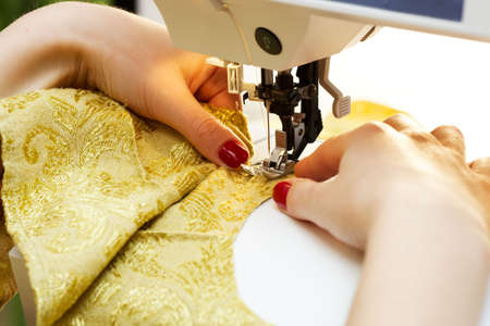 cloth manufacturing: A hand of a dressmaker supporting a cloth while sewing on a sewing machine