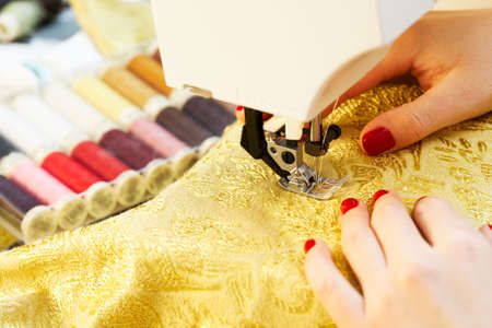 A hand of a dressmaker supporting a cloth while sewing on a sewing machine  photo