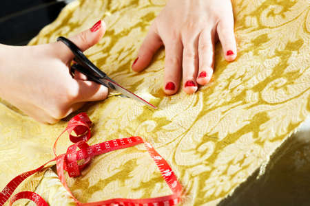 A hand of a dressmaker cutting a cloth  photo