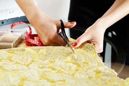 A hand of a dressmaker cutting a cloth  photo