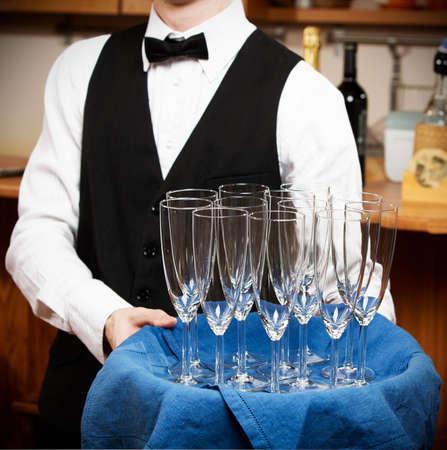barman: professional waiter in uniform is serving wine