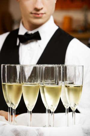glas: professional waiter in uniform is serving wine