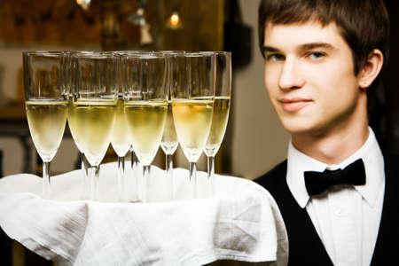 waistcoat: professional waiter in uniform is serving wine