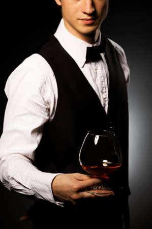 professionelle Kellner in Uniform ist Brandy serviert.
