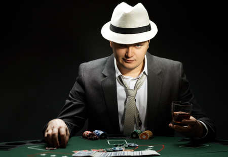 gambler: man wearing hat is playing poker in casino