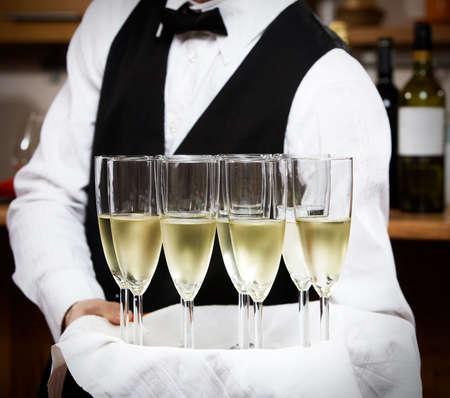 camarero: camarero profesional en uniforme est� sirviendo el vino