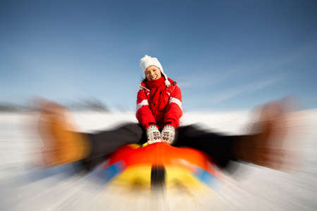 caucasian woman is sliding fast downhill on an inner tube photo