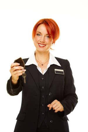 Junge caucasian Frau als Hotel Worker bietet Schlüssel
