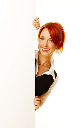 red head woman: adult girl showing on the message on blank billboard Stock Photo