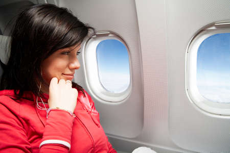 airplane window: young caucasian woman is sitting in the airplane and dreaming