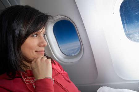 Young caucasian Frau sitzt im Flugzeug und träumen