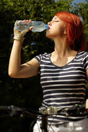 tripping: adult smiling biker woman on mounting bike drinking mineral water