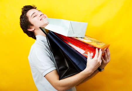 red man: joven cauc�sicos ostenta un mont�n de bolsas de la compra Foto de archivo