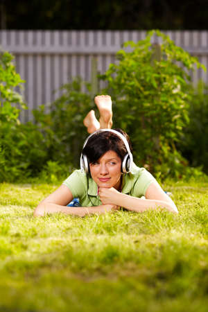 caucasian woman is lying on the grass wearing headphones
