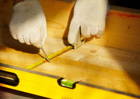 male carpenter is working with wooden plank photo