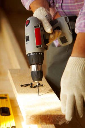 männlich Zimmermann ist mit Holzbrett arbeiten Standard-Bild