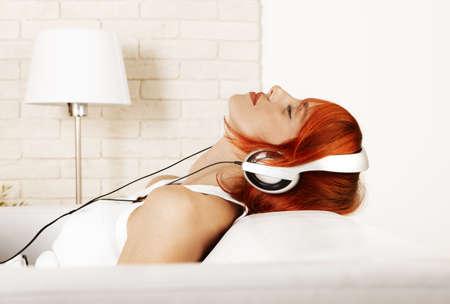Kaukasischen rothaarige Frau mit Kopfhörern und Musik hören