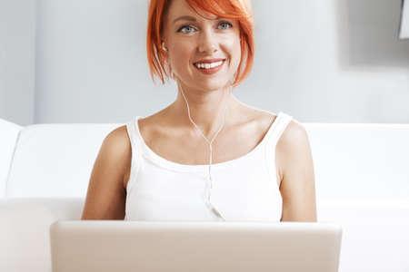 Caucasian redhead woman wearing headphones and listening music photo