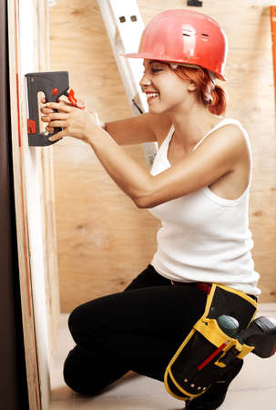 caucasian woman as worker wearing red protective helmet photo