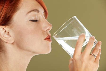 holding head: young red haired woman is drinking mineral water