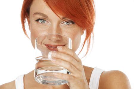 jeune femme aux cheveux rouges est de boire de l'eau minérale Banque d'images