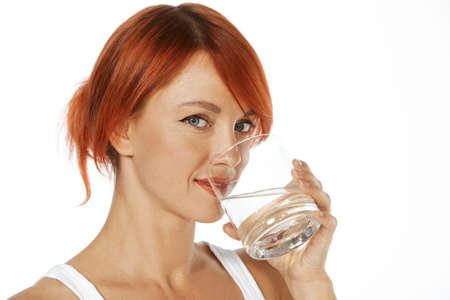 young red haired woman is drinking mineral water photo