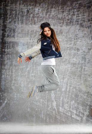 junge, moderne Tänzerin auf dem Boden springen