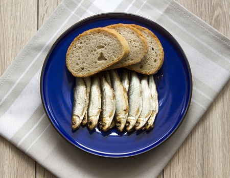 smoked sprats with bread on kitchen table photo