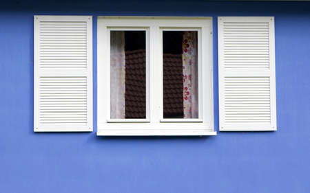 white window with shutters on blue wall