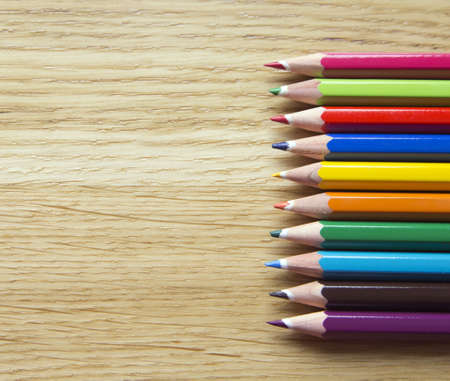 set of colorful crayons on wooden background
