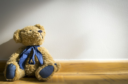 teddy bear toy sitting in front of grey wall