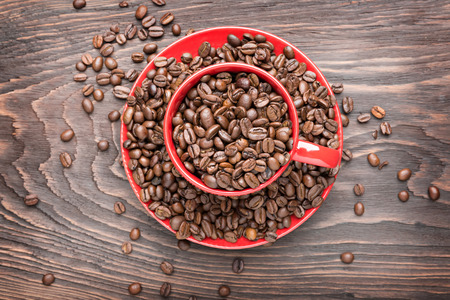 red cup filled with coffee beans on wooden background, flat lay