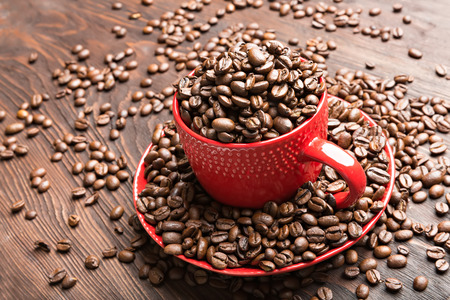 red cup filled with coffee beans on wooden background