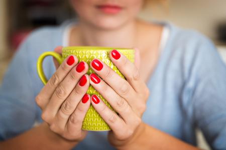shiver: female hands holding a mug of hot beverage