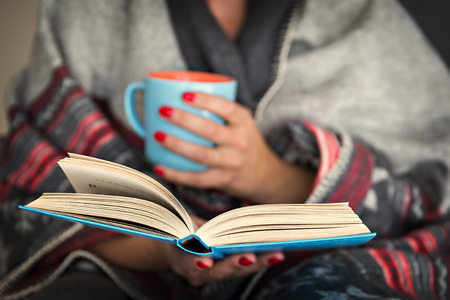 woman reading a book and holding a mug of hot beverage Stock Photo