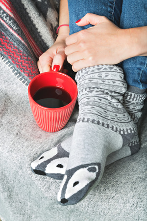 shiver: female legs in cute socks and hand holding a cup of warm beverage Stock Photo