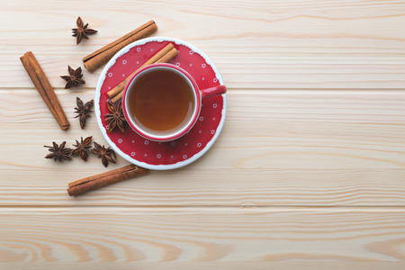 Warm tea in the red cup on the wooden table.
