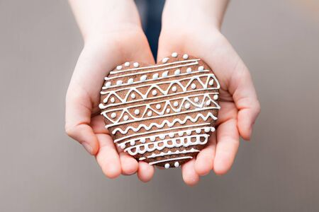 gingerbread cookie: child hands holding gingerbread cookie Stock Photo