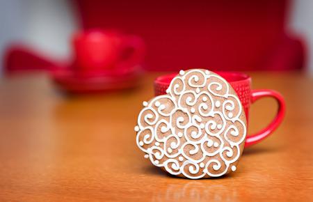 gingerbread cookie: gingerbread cookie standing next to red cup Stock Photo