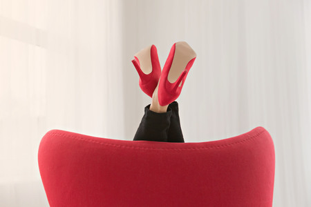 legs in sexy red high heels leaning on the armchair Zdjęcie Seryjne