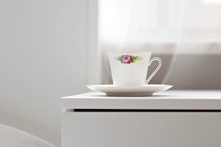 Cup of coffeetea standing on the cupboard in bedroom