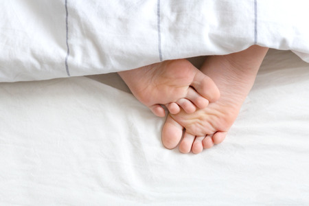 Two feet under the white bedding Stock Photo