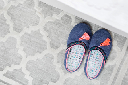 Pair of colorful slippers next to bed Stock Photo
