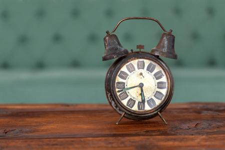 Retro alarm clock on the wooden table