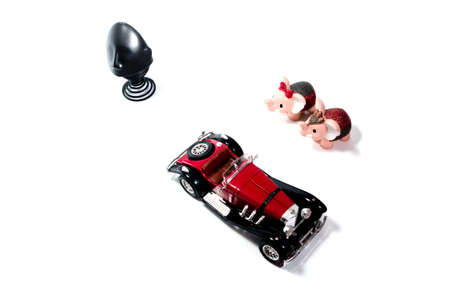 Red toy car and baby elephants looking down from above. Stock Photo